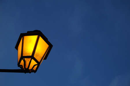 Close up photo of a classic lit street lamp post Stock Photo