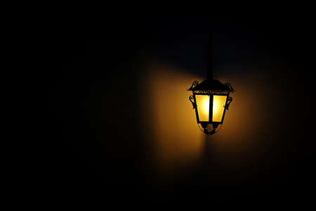 yellow lamp: Photo of a classic lit lamp post, against clear sky, night time.