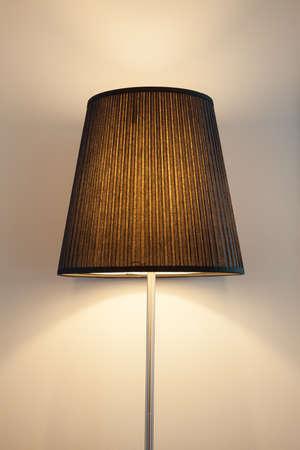 lit lamp: Brown lit lamp against clean cream painted wall.