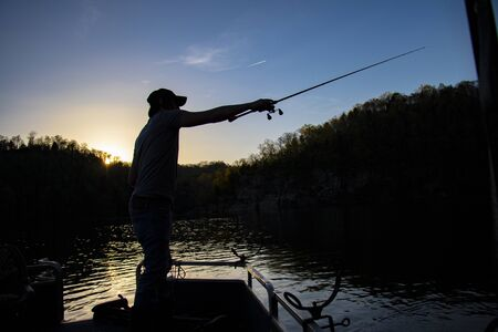 Silhouette of Fisherman Casting Rod and Reel from Boat at Sunset