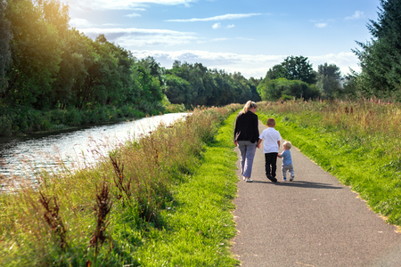 Mother and baby boy walking along path on sunny day Stock Photo