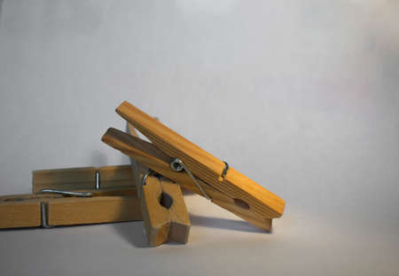A handful of either blue or brown wooden clothespins on a white background.