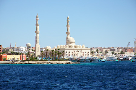 Seascape with ships in the seaport and with a mosque in the background. Hurghada, Egypt Stock Photo