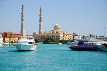 Seascape with motor yachts in marina. View of the mosque in the background