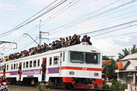 Jakarta, Indonesia, - 9 February 2012 - Young man were ridding on the roof of the commuter train. Editorial