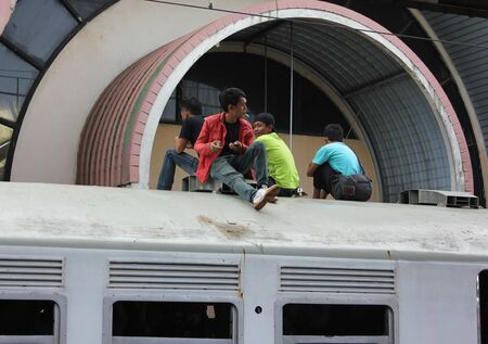 Jakarta, Indonesia, - 18 February 2012 - Young man were ridding on the roof of the commuter train. Stock Photo - 12256170