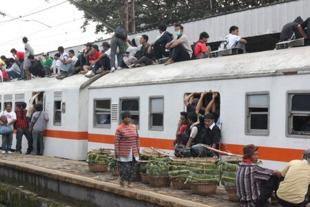Jakarta, Indonesia, 21 February 2012 - Passengers ride on the roof of the commuter train. Editorial