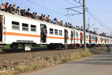 Jakarta, Indonesia, 25 February 2012 - Passengers riding on the rooftop of the commuter train. Stock Photo - 12339490