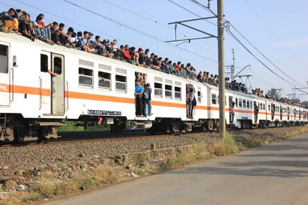 Jakarta, Indonesia, 25 February 2012 - Passengers riding on the rooftop of the commuter train.
