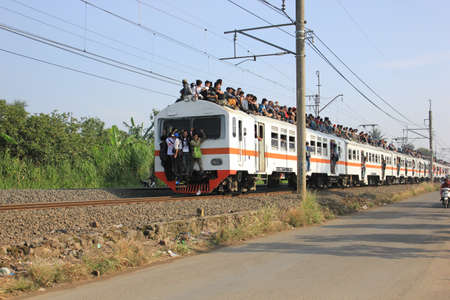 Jakarta, Indonesia, 25 February 2012 - Passengers riding on the rooftop of the commuter train. Stock Photo - 12339492