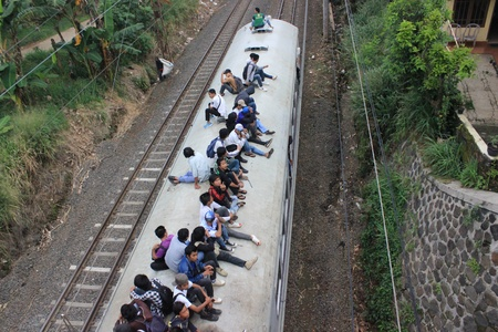 Jakarta, Indonesia, 3 March 2012 - Passengers riding on the rooftop of the commuter train