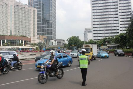 Jakarta, November 22, 2012, police officer directing traffic in downtown Jakarta. Stock Photo - 16742735