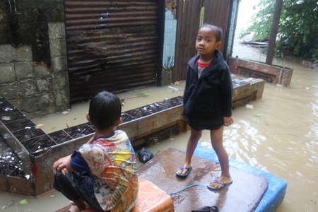 dozens: Jakarta, 17 January 2013, two boys sitting on the simple boat in floods that soak dozens of villages in Jakarta. Editorial