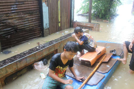 inundated: Jakarta, 17 January 2013, two boys sitting on the simple boat in floods that soak dozens of villages in Jakarta. Editorial