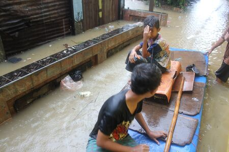 Jakarta, 17 January 2013, two boys sitting on the simple boat in floods that soak dozens of villages in Jakarta. Editorial