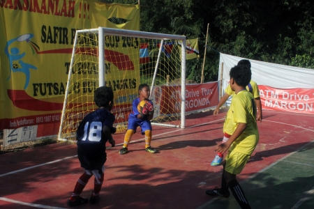 Kids playing futsal in a field in a residential complex in Depok near Jakarta, Sunday, April 9, 2013.