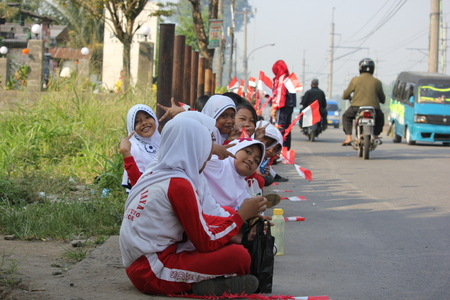 Depok, Indonesia, September 13, 2014 - Elementary school students sitting on the edge of the road to welcome the Indonesian army in order to clean up the river.