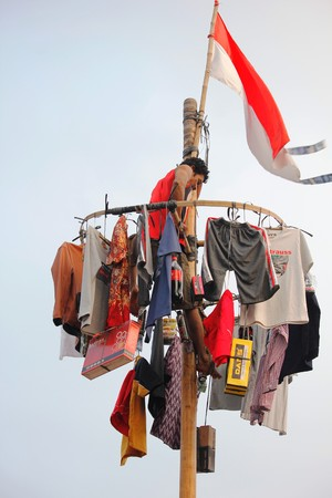 Depok, Indonesia, 17 August 2015 - Nut tree-climbing contest to commemorate Indonesian independence day, in Depok, West Java, Indonesia, August 17, 2015.