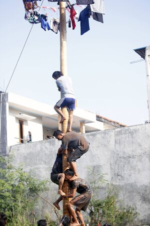Depok, West Java, Indonesia, 17 August 2016 - Participants race to reach the peak of the pole as part the countrys Independence Day celebrations in Depok, West Java, Indonesia on August 17, 2016.