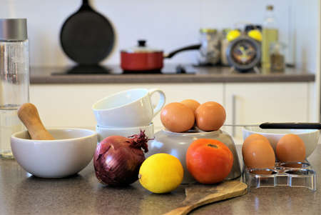 untidy: Crowded Kitchen table with eggs, onion, lemon, tomato, cup on top of another, pestle mortar, wooden spoon, water bottle. In the background are cooking pot, cooking pan, alarm clock.