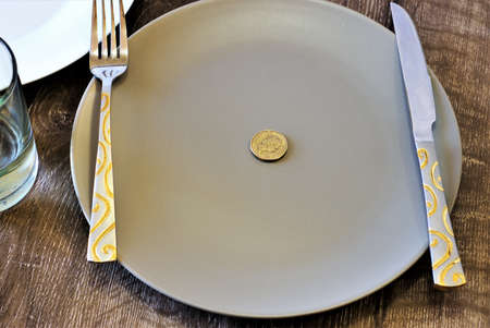 Gold coin on a plate. Australian Dollar coin on a plate with knife and fork 版權商用圖片