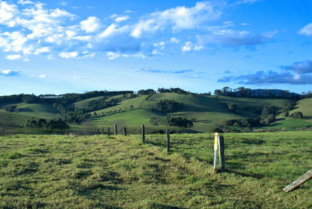 fenced in: Country Scenery of countryside meadows, fenced grass landscape with clouds, blue sky, trees and hills in the far distance in New South Wales, Australia
