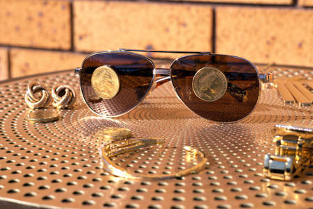 Australian One dollar coins on sunglasses, gold diamond watch and other gold jewelry on table Stock Photo