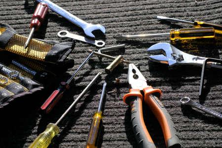 직사광선 아래에서 회색 - 검은 색 작업 매트에 작업자 도구 사용