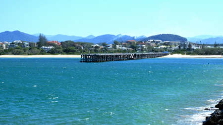 Panoramic view of Jetty Beach and its jetty in Coffs Harbour New South Wales Australia. In view are sea, jetty, beach, real estate, buildings, homes, mountains and sky. Stock Photo
