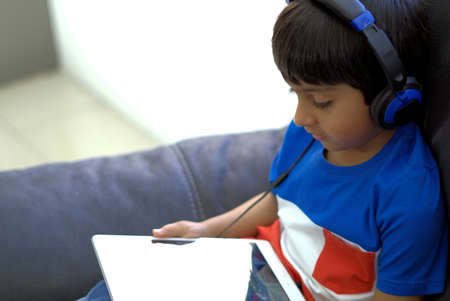 Kid using technology shot in natural light. Kid wearing headphones looking at tablet computer. Child with headphones using tablet. Stock Photo