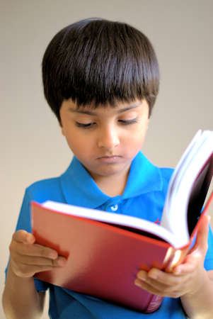 scholarly: Kid reading book. Kid looking into the book, not at the camera. Shot in natural light only.