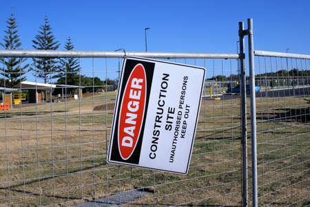 Dangling Sign board Danger Construction Site Unauthorized persons keep out at a construction site in Australia