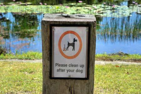 Sign post says Please clean up after your dog at park in Australia.
