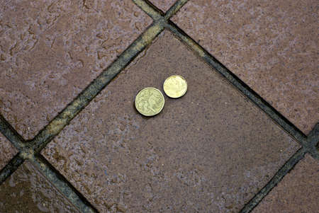 Australian coins outdoors in rain in day light. Australian money on wet surface with small drops of water on one dollar coin and two dollar coin