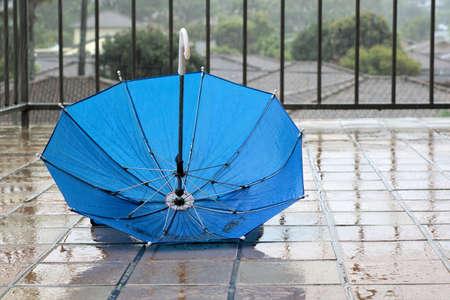 Umbrella in rain. Blue umbrella upside down in rain on wet floor