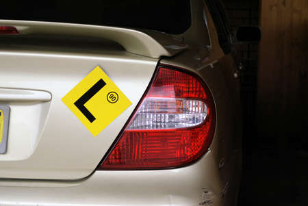 L sign on car with 90 speed limit. Yellow learner's sign. L plate on car Stockfoto - 96674084