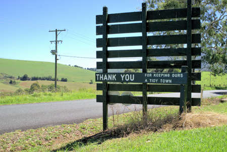 Wooden sign post Thank you For Keeping Ours A Tidy Town next to country road outside the country town of Dorrigo in New South Wales in Australia. Rural area of Australia.