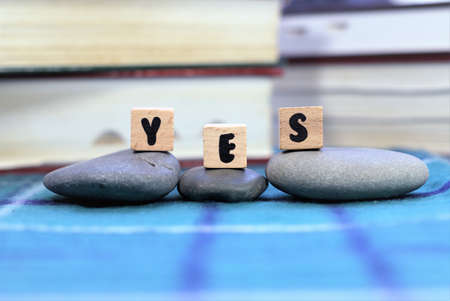 Word Yes on wooden blocks. Selective focus on three letters YES on three wooden cubes placed on three pebble stones. Positive idea or inspirational concept. Фото со стока