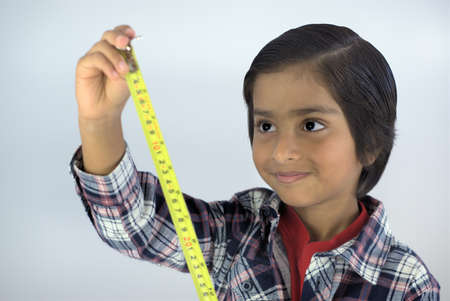 Kid using measuring tape. Smiling kid looking at numbers on tape measure. Concept of measuring height or growing tall.