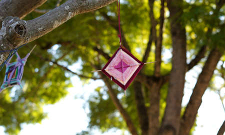 Diamond shaped yarn weaving called God's Eyes ornaments hanging from tree branch. Originated in Mexicos Huichol Indians called Ojo de Dios in Spanish