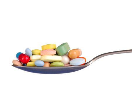 teaspoon: Macro of pills and capsules on a teaspoon Stock Photo