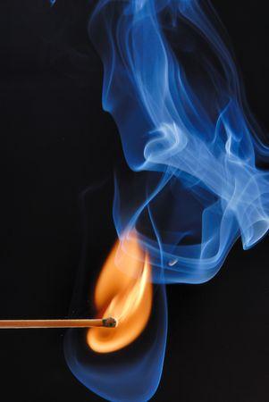 Macro of burning match and smoke on black background photo
