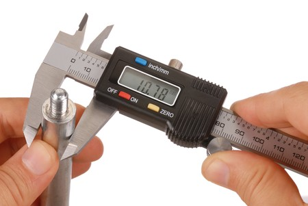 thickness: Digital caliper and hands isolated on white, display set to mm Stock Photo