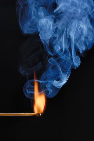 Macro of burning match and smoke on black background photo
