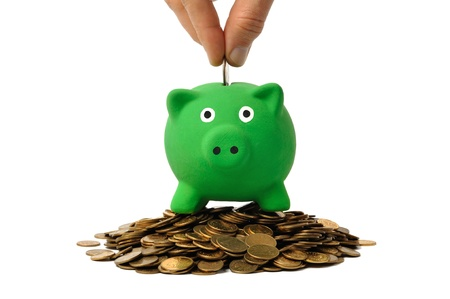 Hand inserting a coin into green piggy bank Stock Photo - 10085420