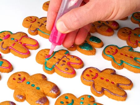 Someone decorating gingerbread cookies on white background