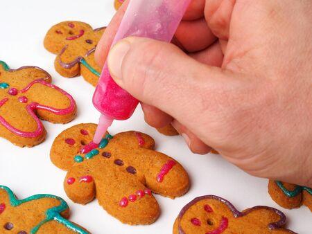 decoracion de pasteles: Alguien decorar galletas de jengibre en el fondo blanco