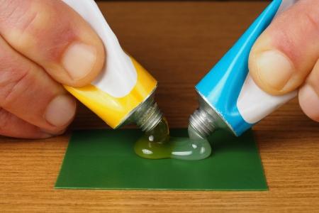 pegamento: Mano que sostiene dos tubos con ingredientes pegamento epoxi, resina y endurecedor