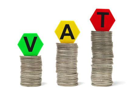 vat: Money stacks and toy blocks with letters forming VAT word