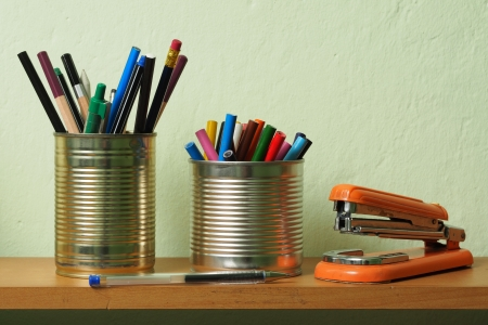 Crayons and pens in waste tin cans standing on a shelf